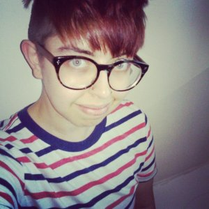 The image features the author, SDF, smilling at the camera. He is an androgynous white person wearing large, round glasses and a striped t-shirt.
