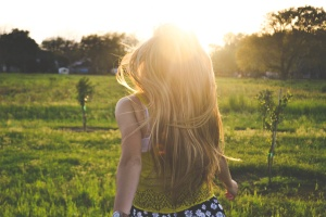 The image features a person with long blonde hair walking toward a grassy field.