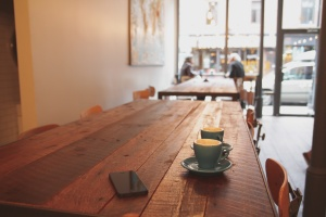 The image features a wooden table with coffee cups on it, with a large storefront window in the distance.